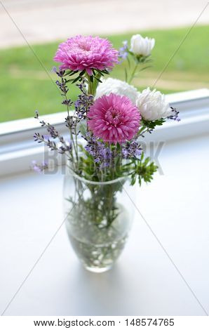 Lavender and asters bouquet on the window sill