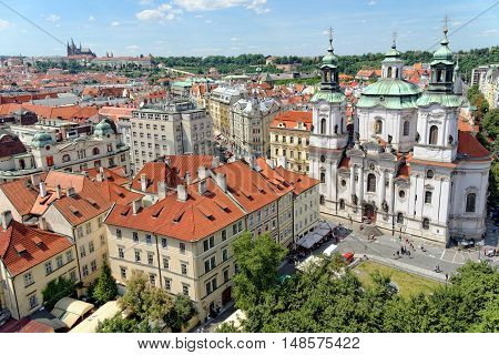 Aerial view of the traditional red roofs of the city of Prague Czech Republic with Prague castle in the distance and St. Nicholas church in the Old Town Square.