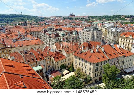 Aerial view of the traditional red roofs of the city of Prague Czech Republic with Prague castle and Petrin Hill in the distance and New city hall with the sculptures on the roof.