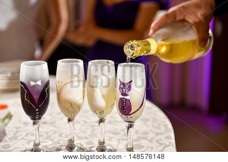 Hand man pours champagne into wedding glasses