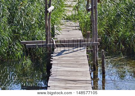 Closeup of an old and abandoned wooden bridge over the river