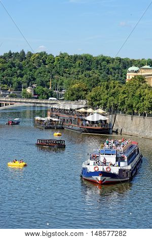 PRAGUE, CZECH REPUBLIC - JULY 3, 2014: View of the Vltava river with cruise tour boats from the Charles Bridge. The Charles Bridge is a famous historic bridge that crosses the Vltava river.