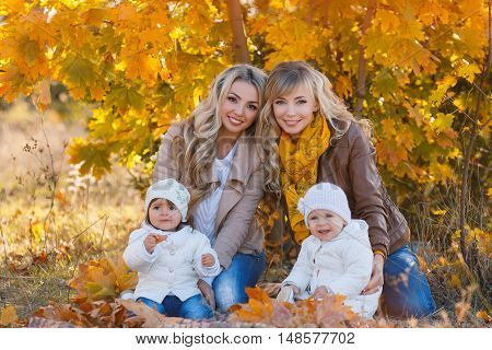 Two beautiful young mom,two blondes with long curly hair,dressed in blue jeans and leather jackets,walk in the Park day on the background of beautiful yellow autumn nature with young daughters,dressed in white jackets,white hats and blue jeans
