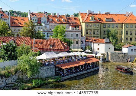 Houses and restaurants on the right bank of the river Vltava in Prague Czech Republic.
