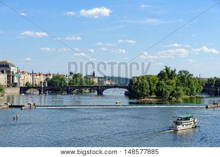 View of the Vltava river with cruise tour boats from the Charles Bridge. The Charles Bridge is a famous historic bridge that crosses the Vltava river in Prague Czech Republic.