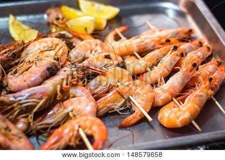 Classic tiger shrimp skewers. Shrimps sriracha kebabs with lemon for dinner. Delicious prawn spit prepared on grill. Extreme close up of appetizing grilled queen prawn on the tray.