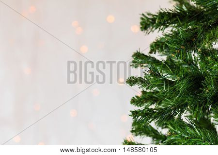 Festive Christmas close up background of bare artificial pine tree. Subtle bokeh copy space.