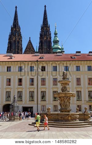 PRAGUE, CZECH REPUBLIC - JULY 4, 2014: The baroque fountain in the second courtyard of the Prague Castle and the towers of the St. Vitus Cathedral.