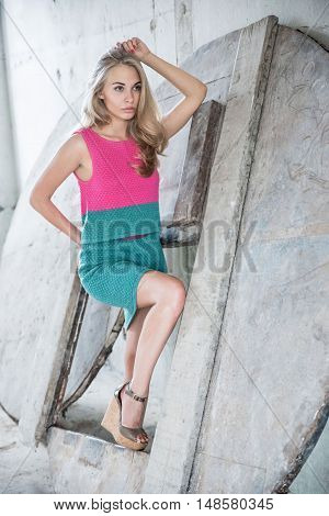 Beautiful blond woman in dress posing in studio