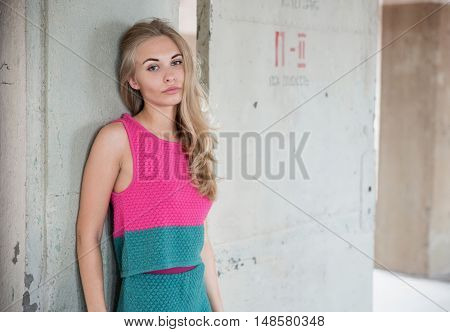 Beautiful and young blond woman in dress posing in studio