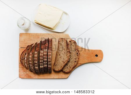 Loaf of freshly baked brown rye wheat whole grain homemade bread with sliced pieces on a wooden cutting board with salt and butter isolated on white table background Natural organic food ingredients for sandwich