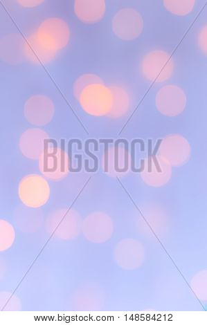 Sparkly bokeh lights background pastel pale blue and peach. Vertical.