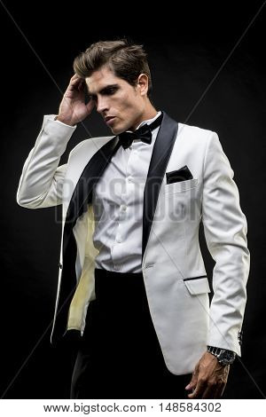 Success, elegant man in a white suit tuxedo with bow tie around his neck