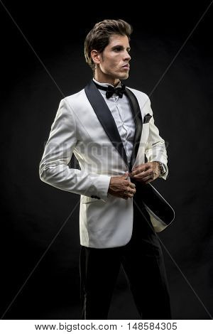 Evening, elegant man in a white suit tuxedo with bow tie around his neck