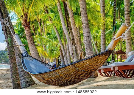 Romantic empty cozy hammock in the shadow of the palm on the tropical beach by the sea Maenam Beach Koh Samui Thailand. Holiday and vacation concept.