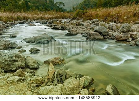 Beautiful Reshi River water flowing through stones and rocks at dawn Sikkim India. Tinted image. Reshi is one of the most famous rivers of Sikkim flowing through the state and serving water to many local people.
