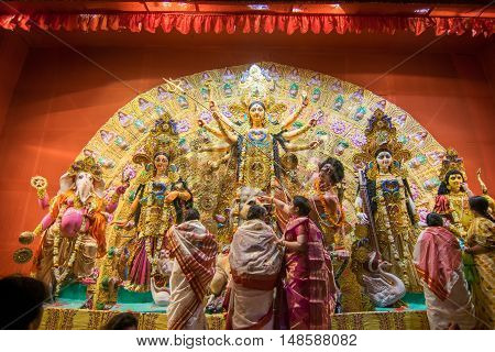 KOLKATA INDIA - OCTOBER 18 2015 : Married Bengali women worshipping Durga idol at Puja pandal shot at colored light at Kolkata West Bengal India. Durga Puja is biggest religious festival of Hinduism.
