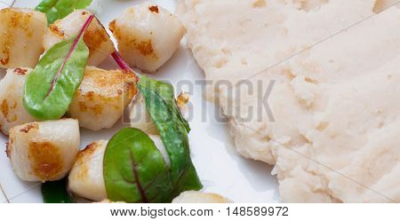 Grilled scallops with mashed beans and beet leaves