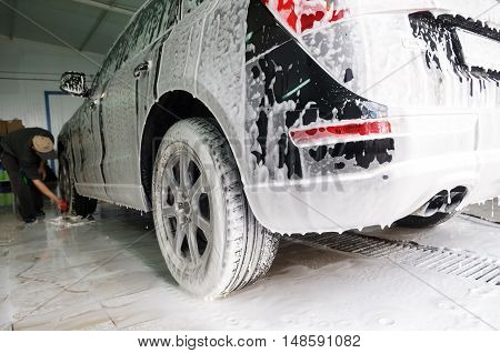 Worker washing car with wash cleaning foam