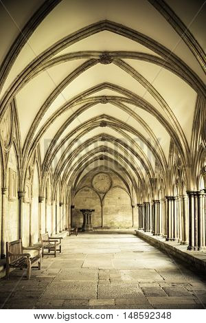 The vaulted ceiling of Salisbury Cathedral Cloisters, an exterior covered walkway around the outside wall of the building. Retro style sepia processing.