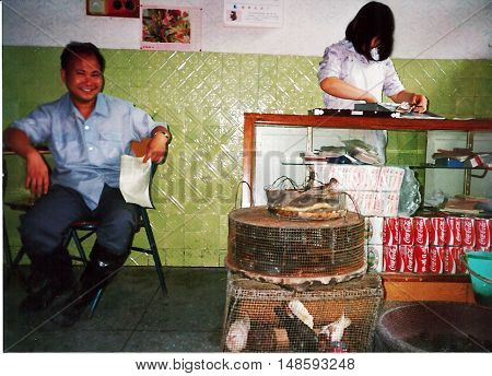 GUILIN / CHINA - CIRCA 1987: A restaurant owner smiles for a photograph inside his restaurant in Guilin.
