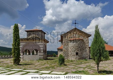 Giginski monastery, Bulgaria - June 25, 2016:  View of inner  yard with old medieval church, alcove and  bell tower  in restored Montenegrin or Giginski monastery  St. St. Cosmas and Damian, mountain  Kitka, Breznik, Pernik region, Bulgaria. Visit in the