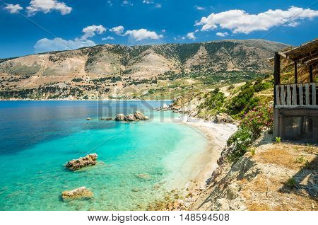 Vouti beach, Kefalonia island, Greece. People relaxing at the beach. The beach is surrounded by flowers.