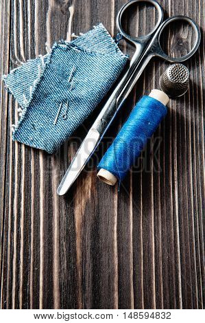 Jeans, blue thread, needle and scissor on wooden background dark tone - rustic style, top view
