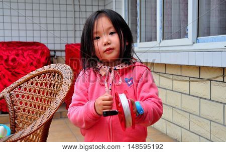 Pengzhou China - March 27 2015: Litle Chinese girl playing with a kite reel in front of her home  *