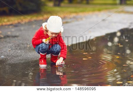 happy child girl playing with autumn leaves in a puddle after a rain in autumn