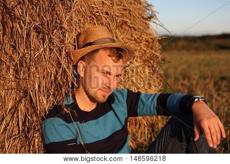 THE MAN YOUNG IN THE FIELD ON THE HAYSTACK IN THE STRAW HAT
