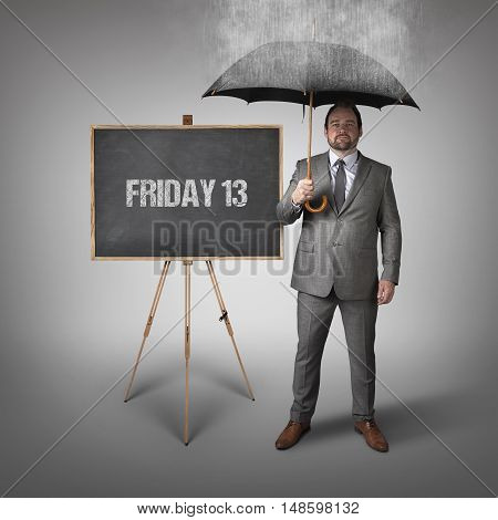 Friday 13 text on blackboard with businessman and umbrella