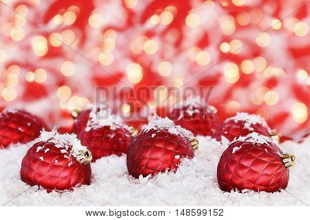 Beautiful ornate glass Christmas ornaments lying in the snow against a red and gold bokeh background. Shallow depth of field with selective focus on baubles in foreground.