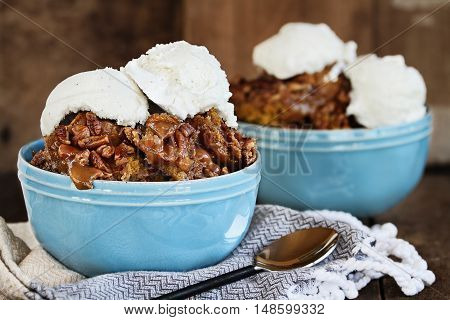 Hot autumn dessert pumpkin cobbler made with pumpkin spice and pecans with creamy french vanilla ice cream against a dark rustic moody background.
