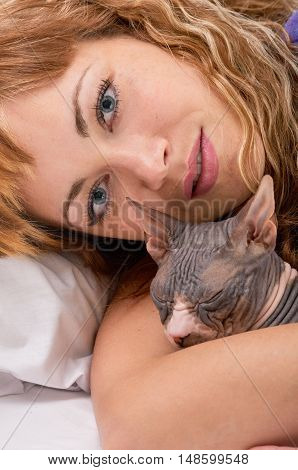 pretty young woman with her cat sphynx on the bed at home, shot from above