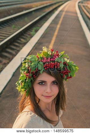 portrait of a girl with a wreath on his head against the background of the railway