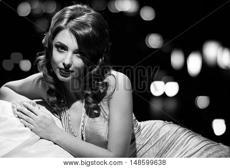 woman in dress studio portrait in hollywood style light with night lights city background. in black and white toning