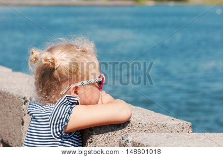The girl in the summer in hot weather is on the river bank in sunglasses