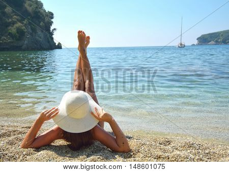 Woman enjoying sunny day on beach with beautiful landscape