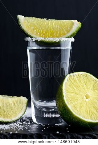 Tequila silver shot with lime slices and salt on grunge wooden board