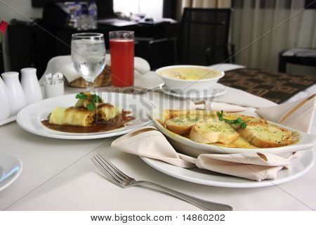 Room service food presentation with hotel bed in background