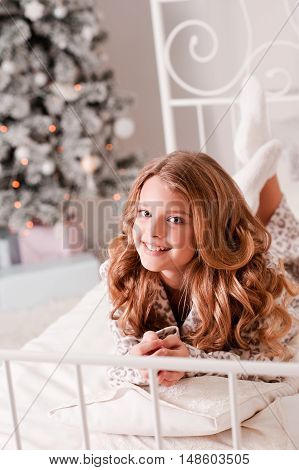 Smiling blonde teen girl 14-16 year old lying in bed over christmas tree in room. Looking at camera.