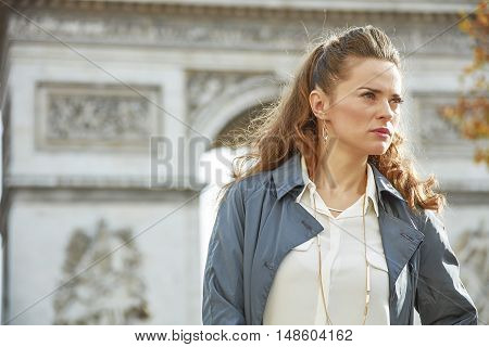 Stylish autumn in Paris. trendy woman in trench coat in Paris France looking aside