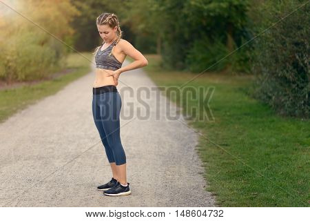 Woman Athlete Pausing To Relieve Her Back Pain