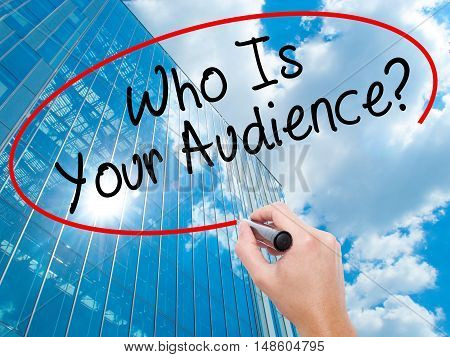 Man Hand Writing Who Is Your Audience? With Black Marker On Visual Screen