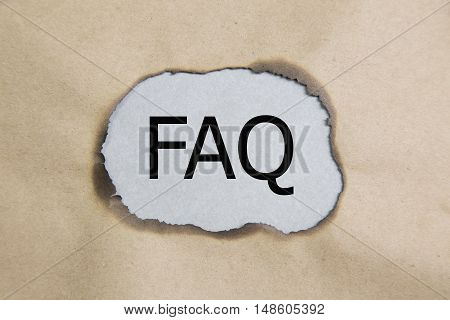The acronym FAQ - Frequently Asked Questions appearing behind torn paper.