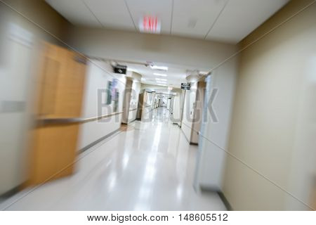 Rushing down a well lit hospital corridor with heavy oak doors leading to cardiology