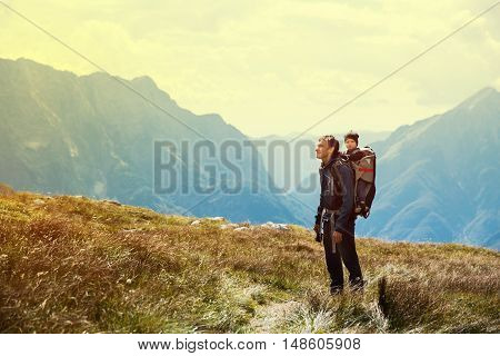 Father hiking with child in carrier backback on the background of mountains. Family on trekking day in the mountains. Mangart, Slovenia, Europe. Travel, Lifestyle Concept. Photo toning warm colors