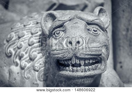 Ancient sculpture of a lion or tiger's head.