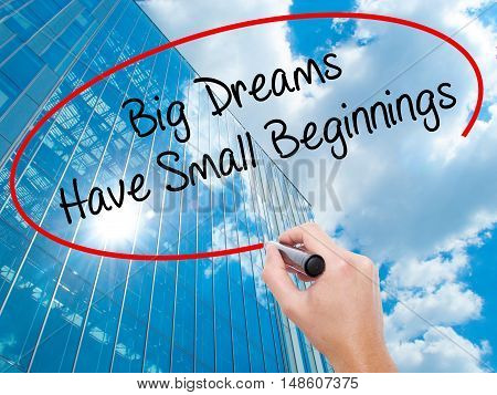 Man Hand Writing Big Dreams Have Small Beginnings With Black Marker On Visual Screen